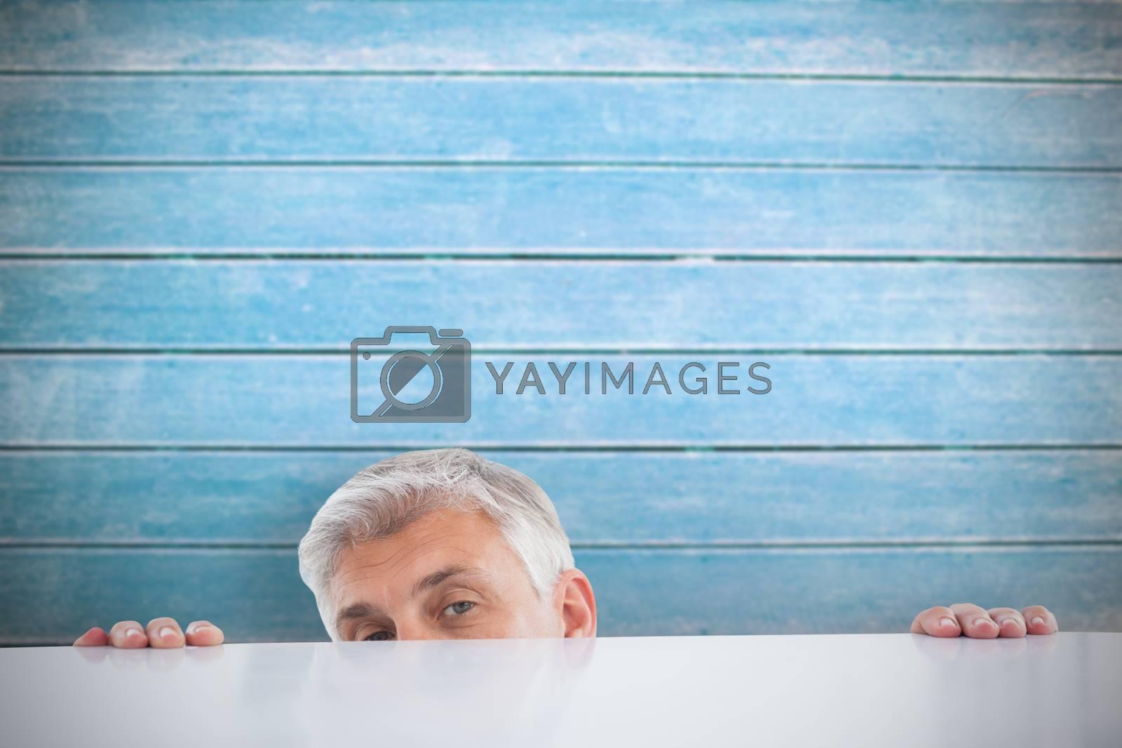 Businessman peeking over desk against wooden planks