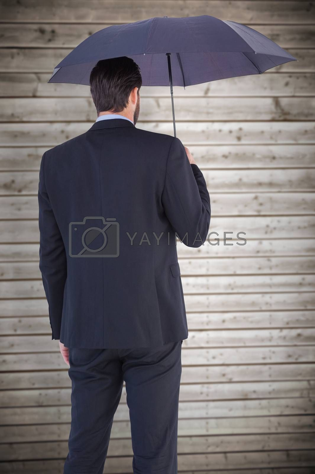 Businesswoman in suit holding umbrella against wooden planks background