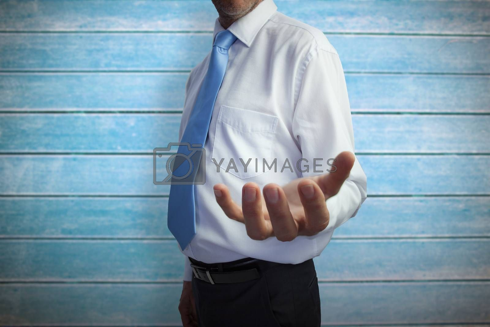 Businessman holding hand out against wooden planks
