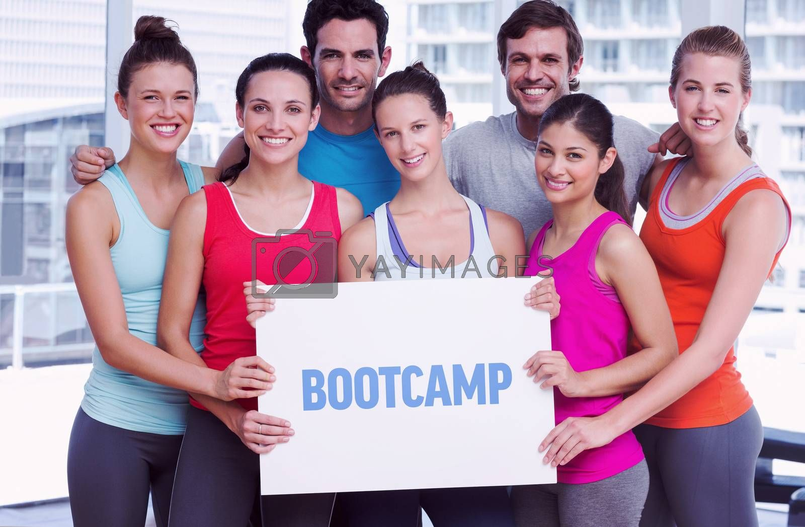 Bootcamp against fit smiling people holding blank board by Wavebreakmedia