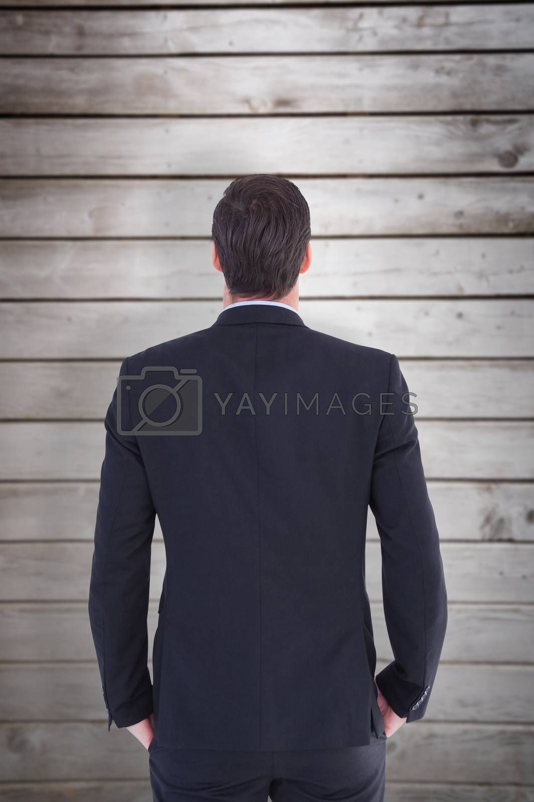 Rear view of handsome businessman  against wooden planks