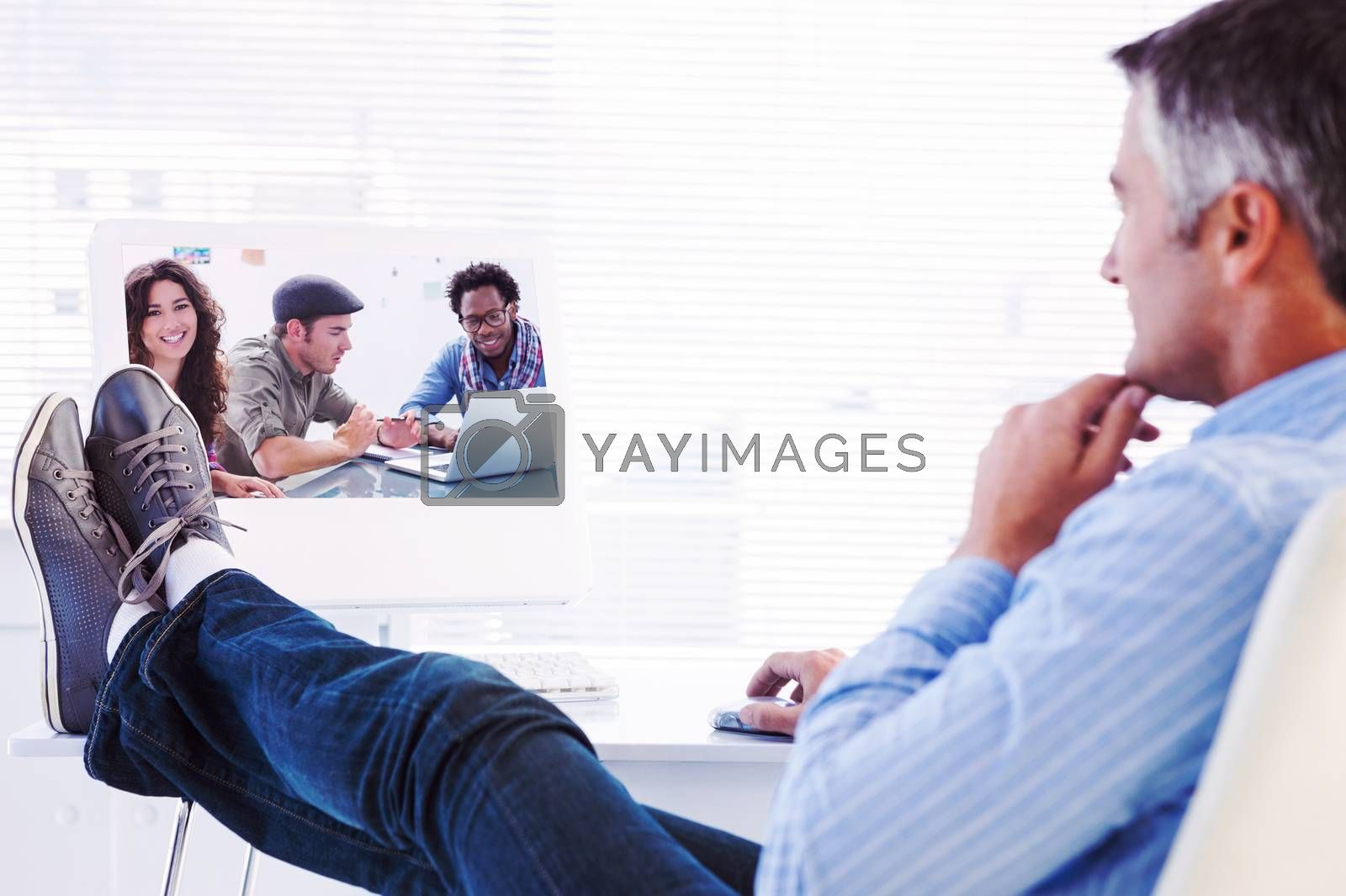 Relaxed man with feet on desk using computer against creative team working together with one smiling at camera