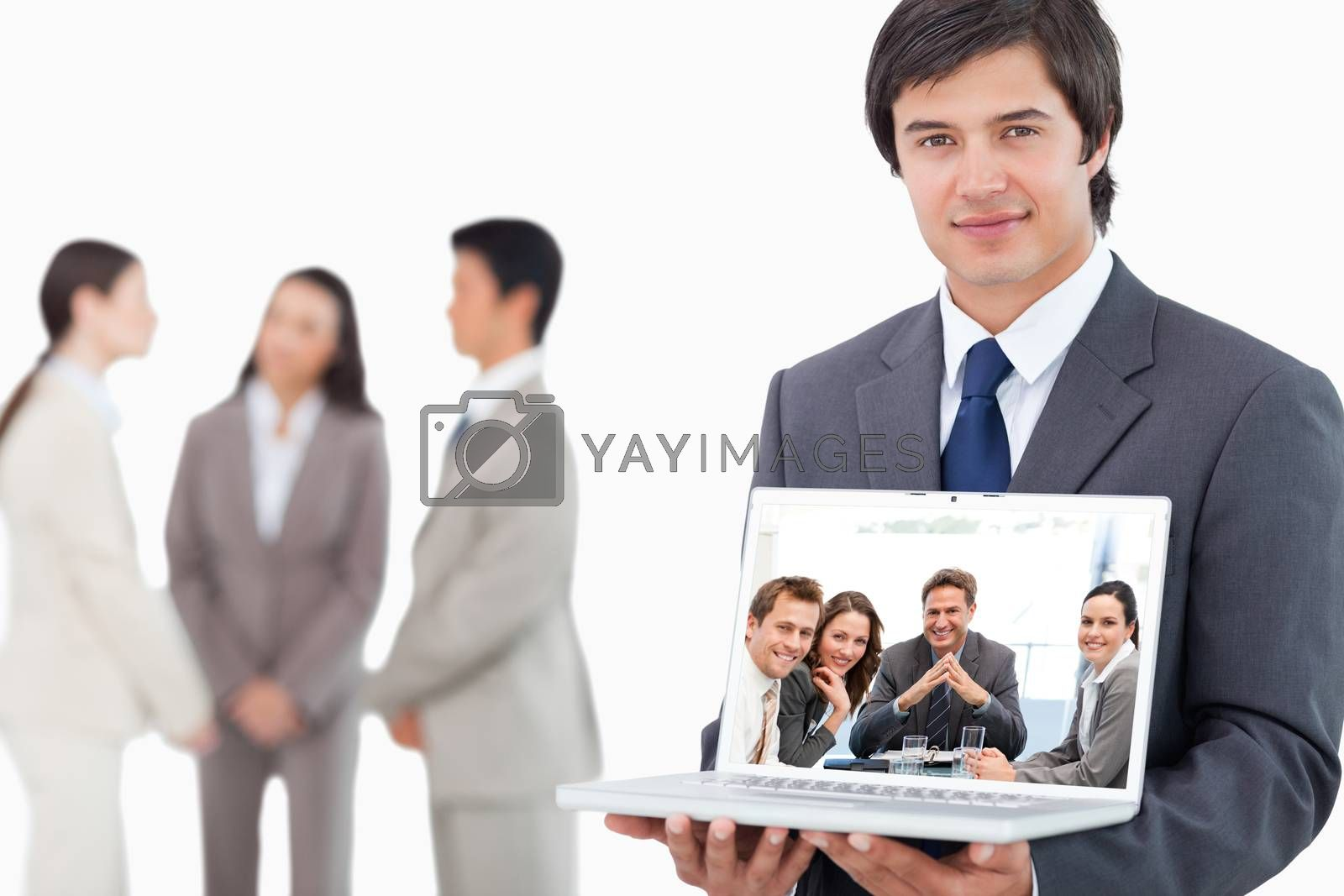 Portrait of a positive manager with his team against salesman showing laptop screen with colleagues behind him