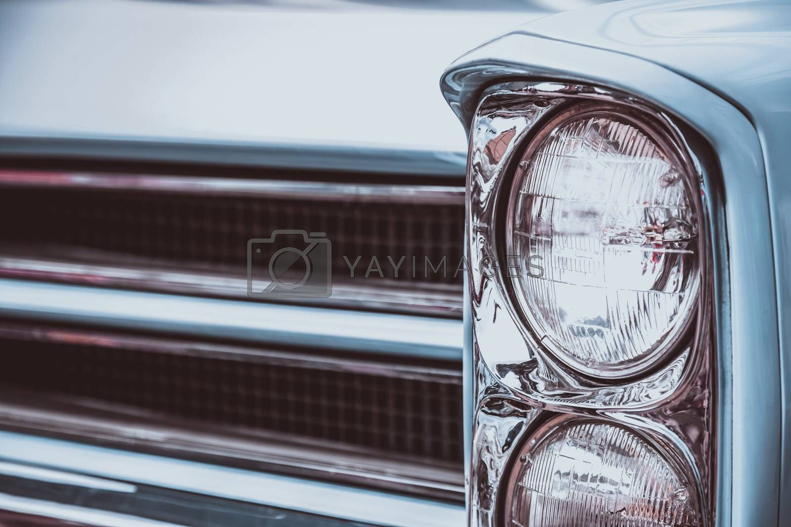Front lights and radiator grill of an old vintage automobile. Processed by vintage or retro effect filter