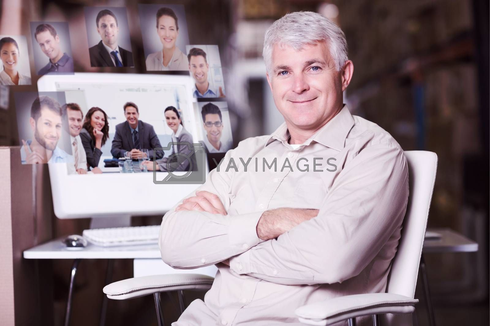 Warehouse manager using computer against portrait of a positive team sitting at a table