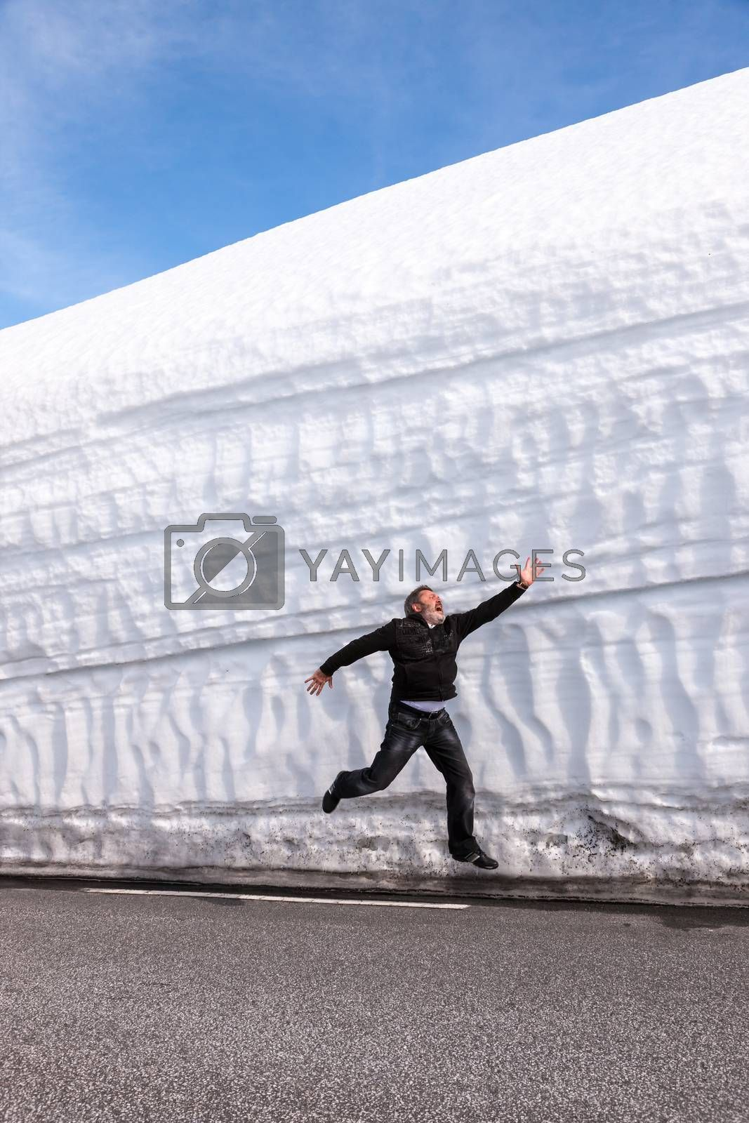 man running on the highway along the snow wall. Norway in the spring