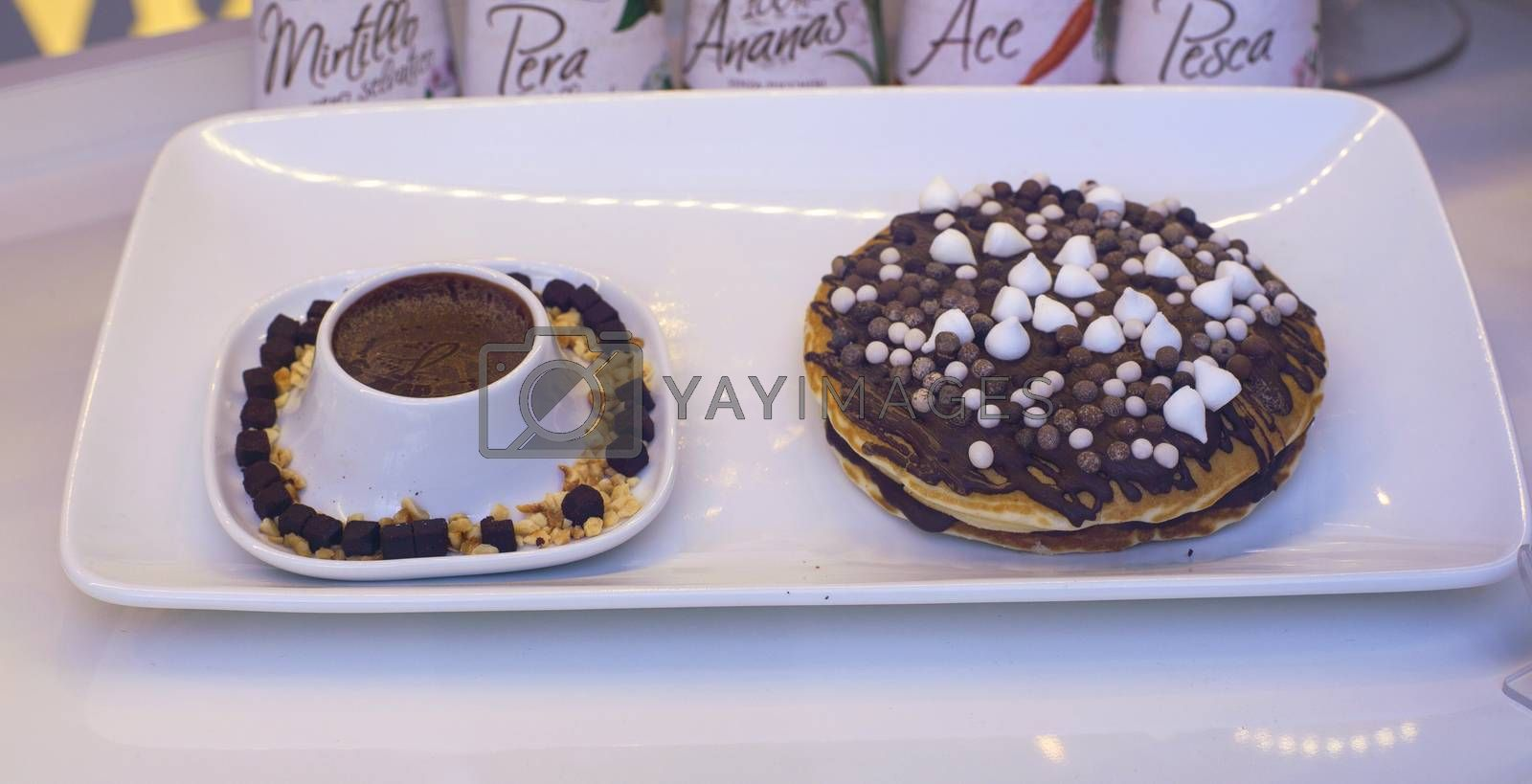 Close up of cup of chocolate and brioches with candie