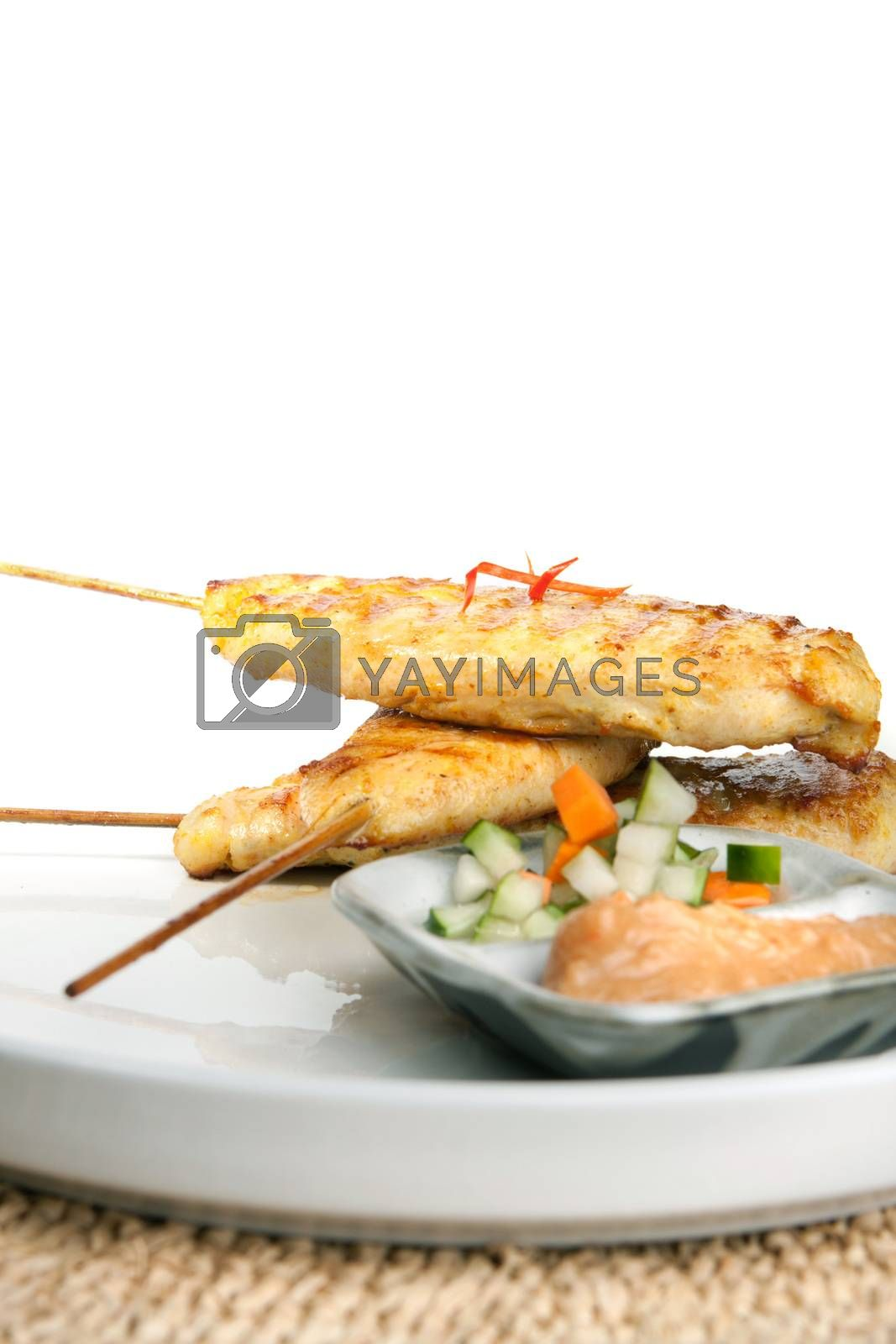 Asian style chicken satay barbecued chicken on skewers with peanut dipping sauce.