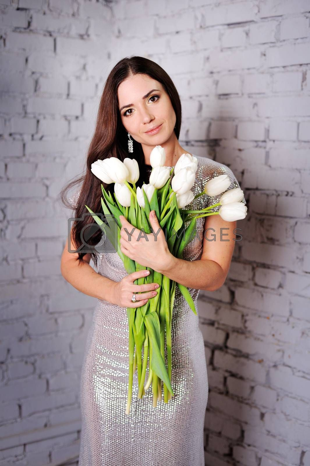 Beauty Woman with Spring Flower bouquet. Beautiful girl with a Bouquet of Tulip flowers. Happy surprised model woman smelling flowers. Mothers Day