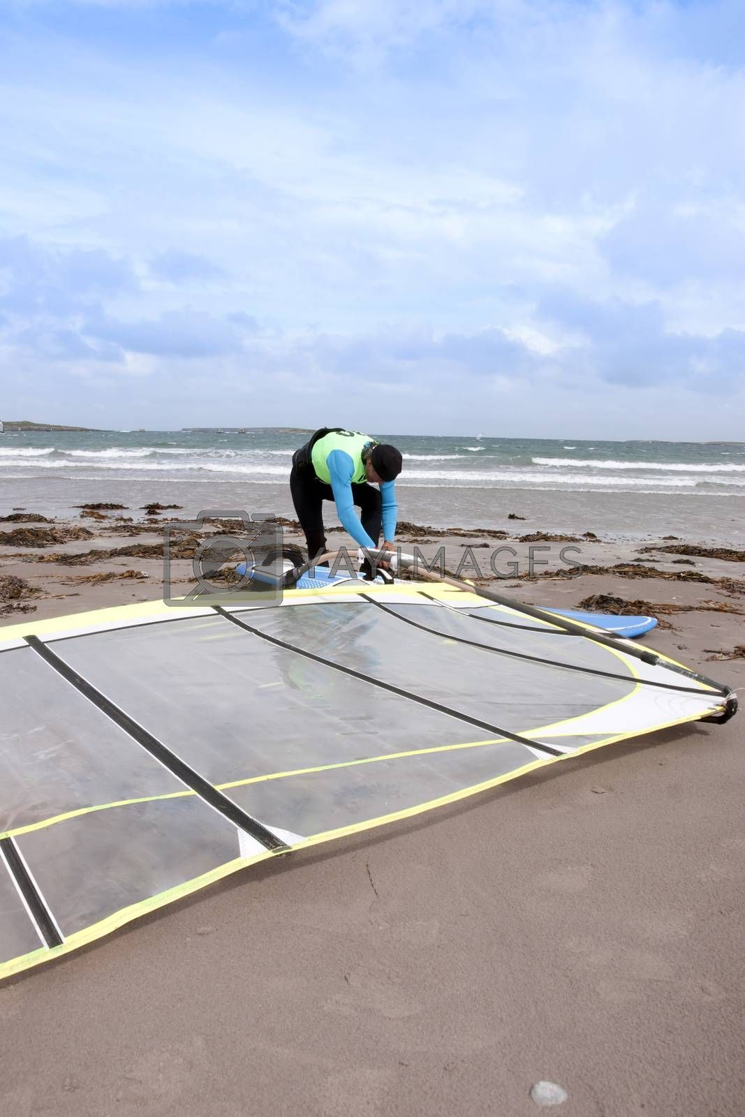 windsurfer getting equipment ready on the beach in the maharees county kerry ireland