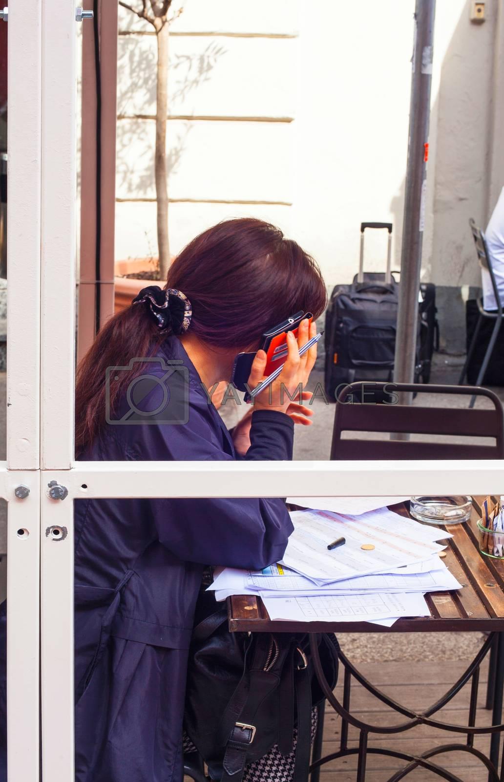 Businesswoman talking on smartphone by bepsimage