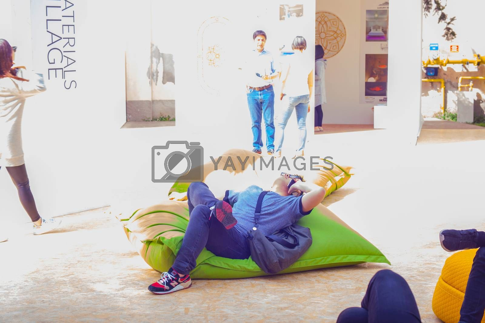 Young man talking on smartphone while lying on green pouf  by bepsimage