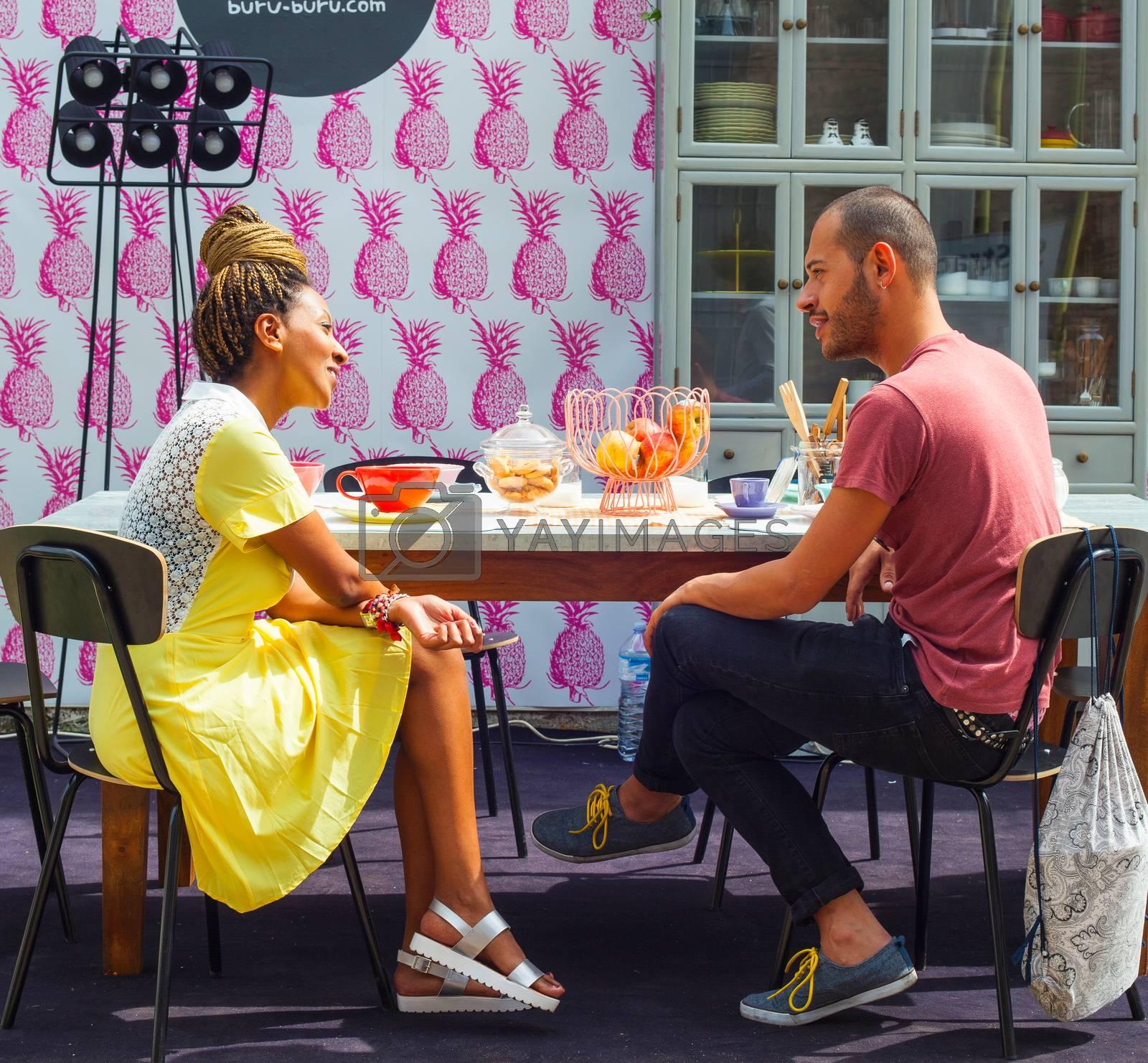 MILAN, ITALY - APRIL 16: Couple of friends enjoying a conversation in the kitchen room at Buru-buru stand in theTortona space location during Milan Design week on April 16, 2015