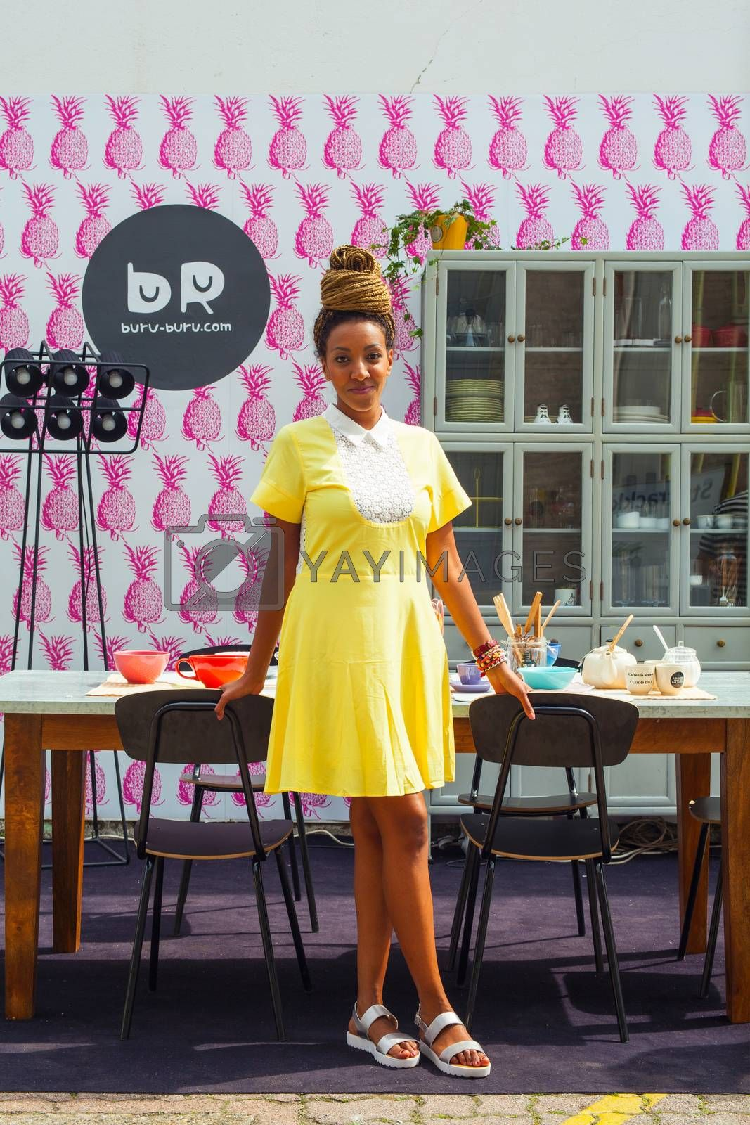 MILAN, ITALY - APRIL 16: Pretty young black girl in the kitchen room at Buru-buru stand in the Tortona space location during Milan Design week on April 16, 2015