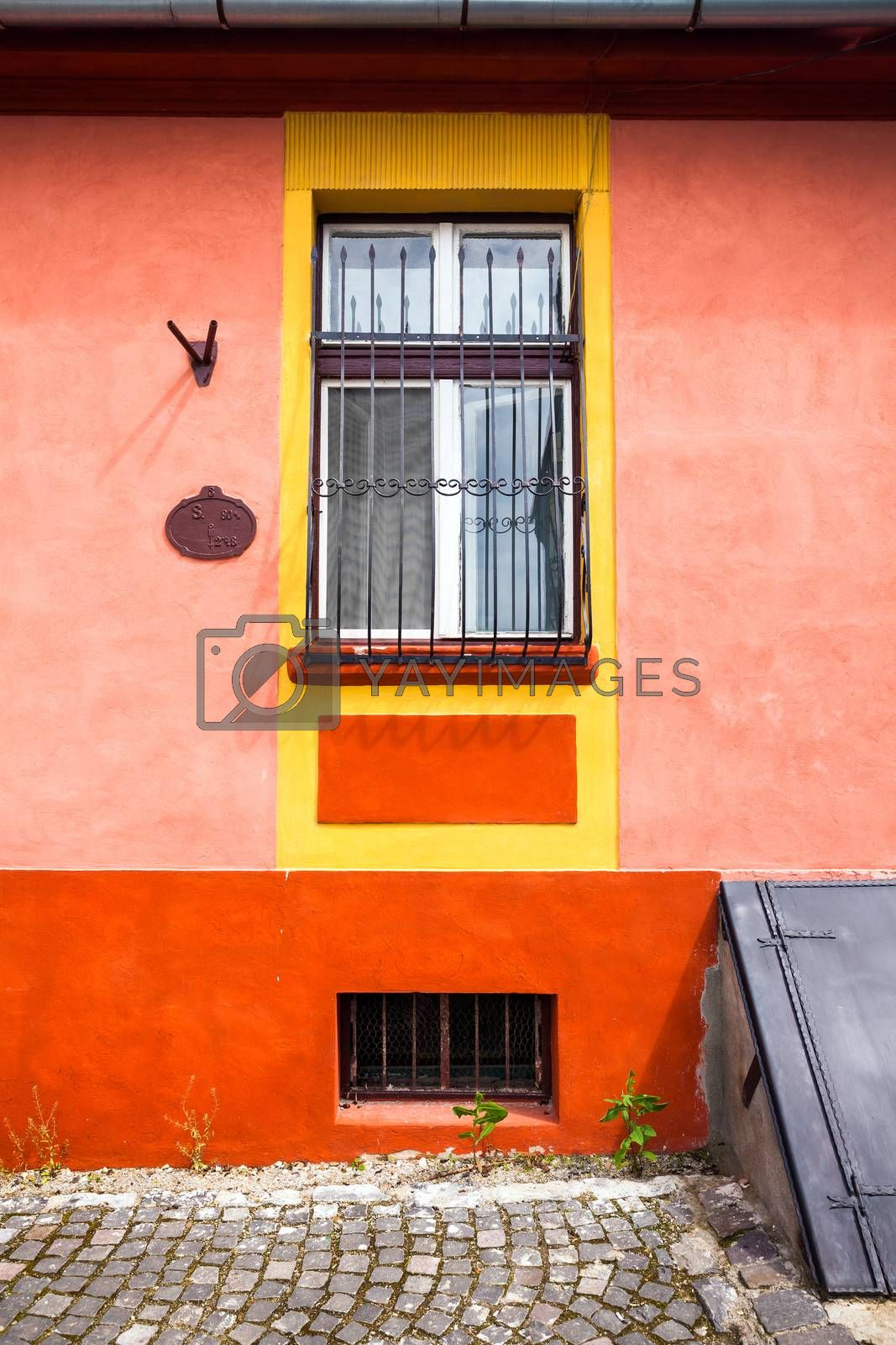 Sighisoara, Romania - June 23, 2013: Orange house facade with wooden window from Sighisoara city old center, Transylvania, Romania