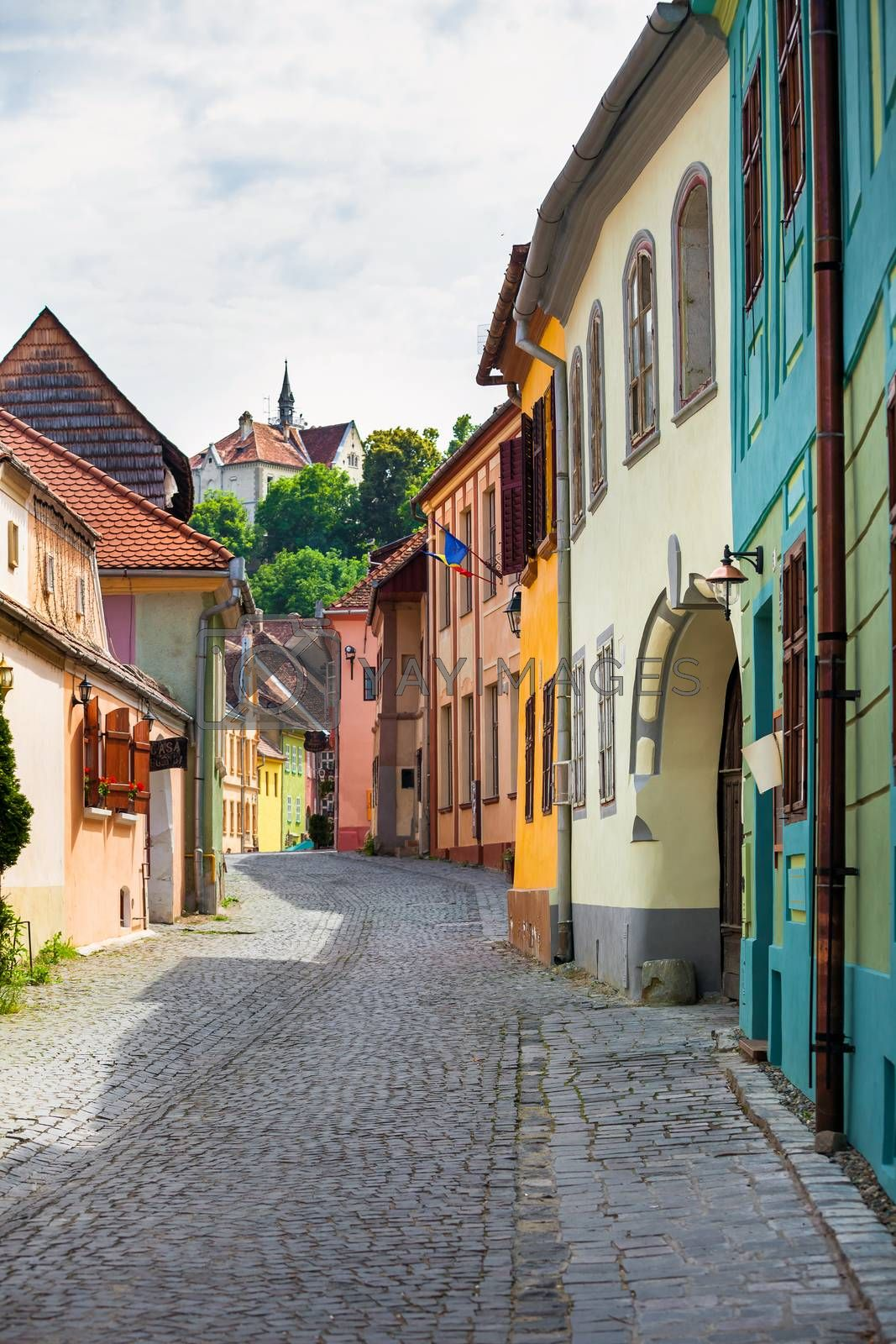 Sighisoara, Romania - June 23, 2013: Stone paved old street with colored houses from Sighisoara fortresss, Transylvania, Romania