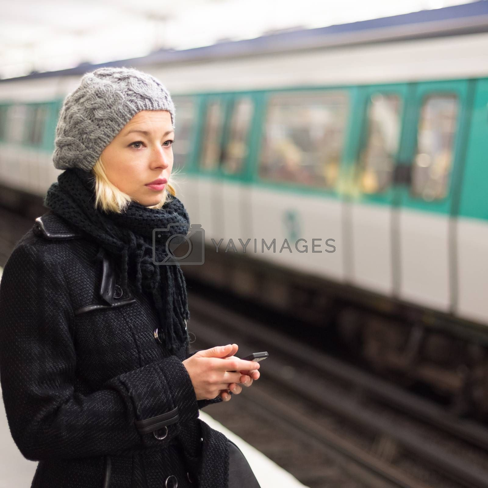 Young woman in winter coat with a cell phone in her hand waiting on the platform of a railway station for train to arrive. Public transport.