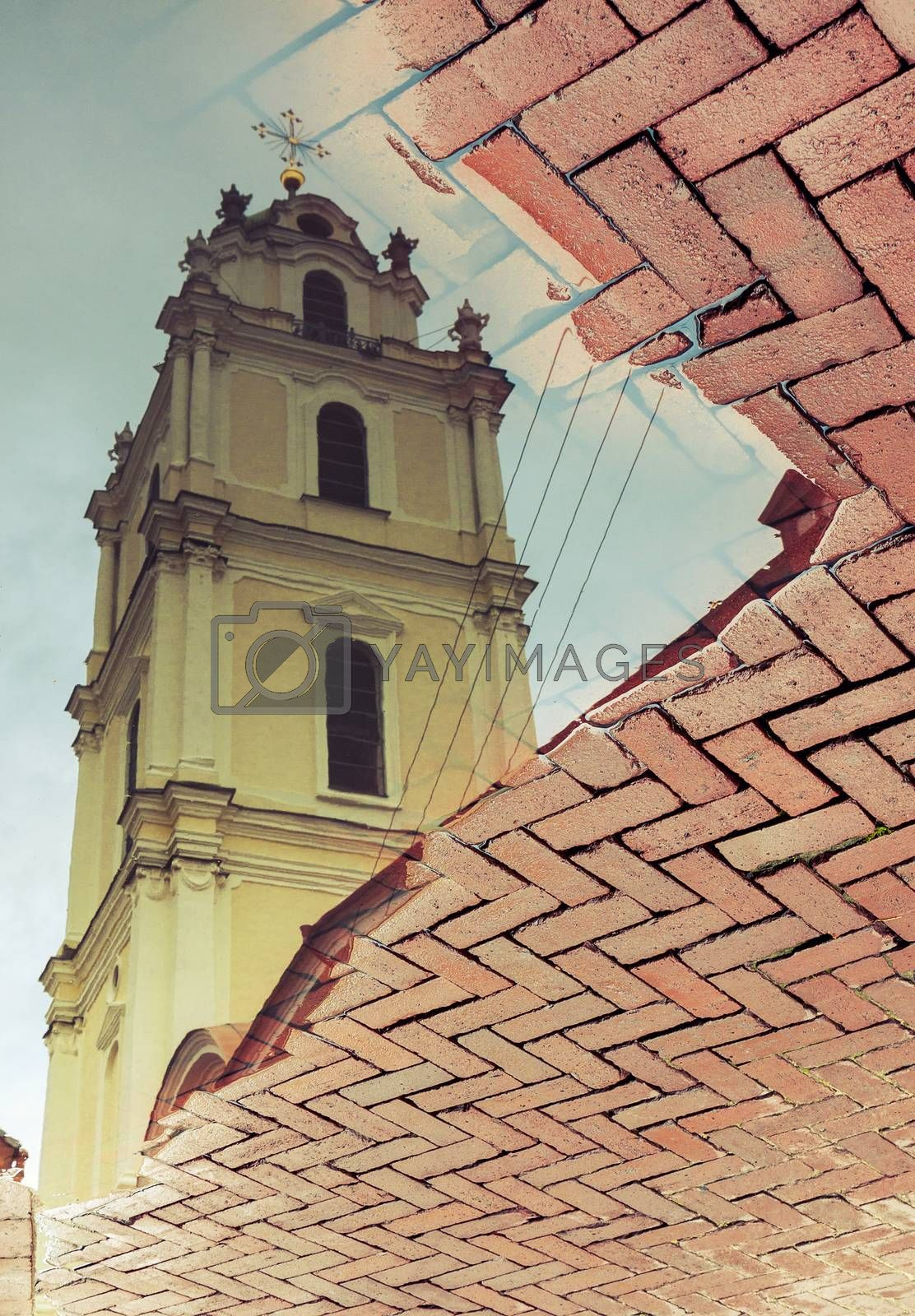 Old church in Vilnius, Lithuania, reflected in water puddle on cobblestone pavement
