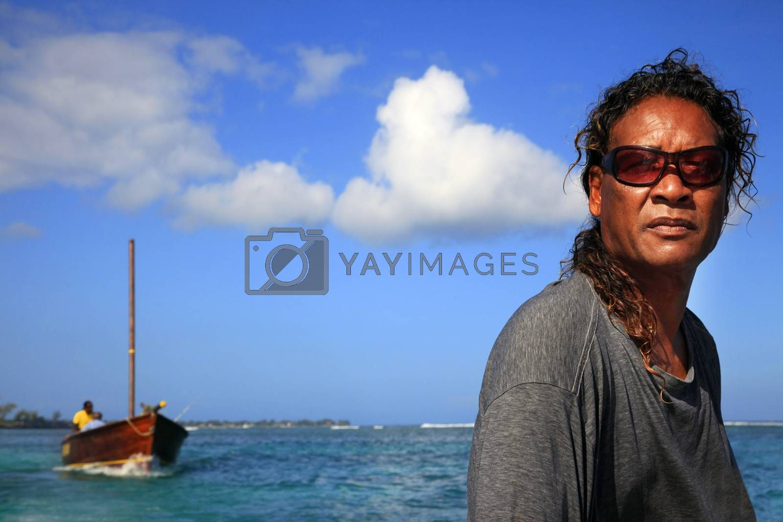 Pereybere, Mauritius - January 21, 2012: Unknown adult fisherman Creole posing in front of their boat on Island Mauritius.
