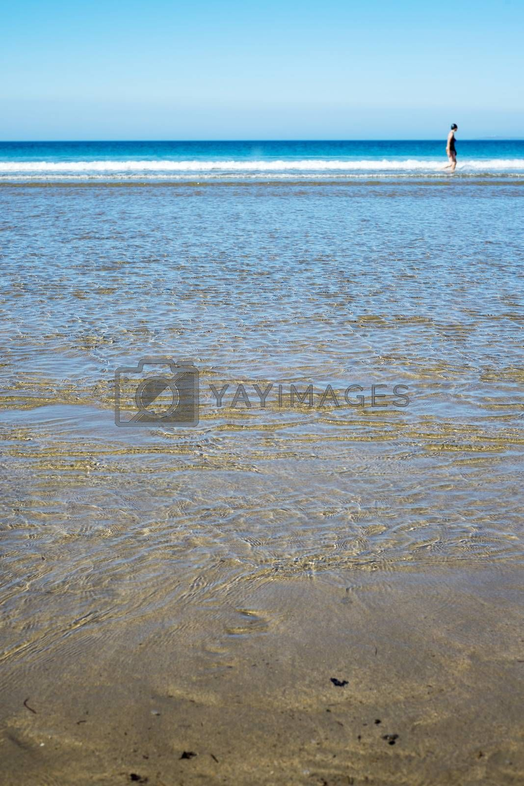 calm soft waves lashing onto ballybunion beach in county kerry ireland with wading woman