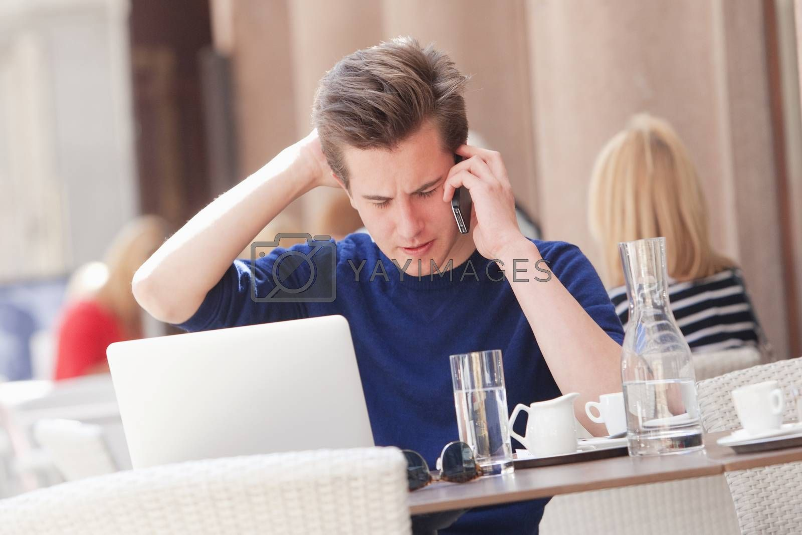 Royalty free image of Young Man Sitting in Outside Coffeehouse Talking on Phone by courtyardpix
