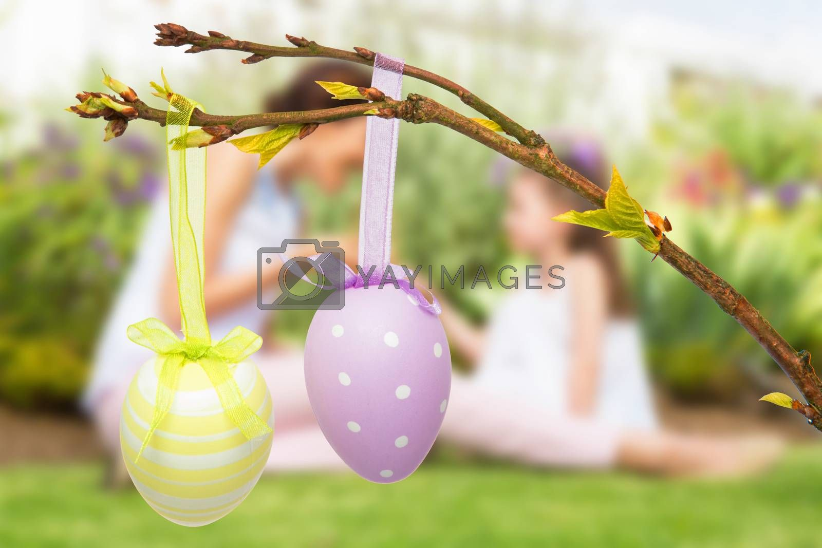 Mother and daughter collecting easter eggs against hanging easter eggs
