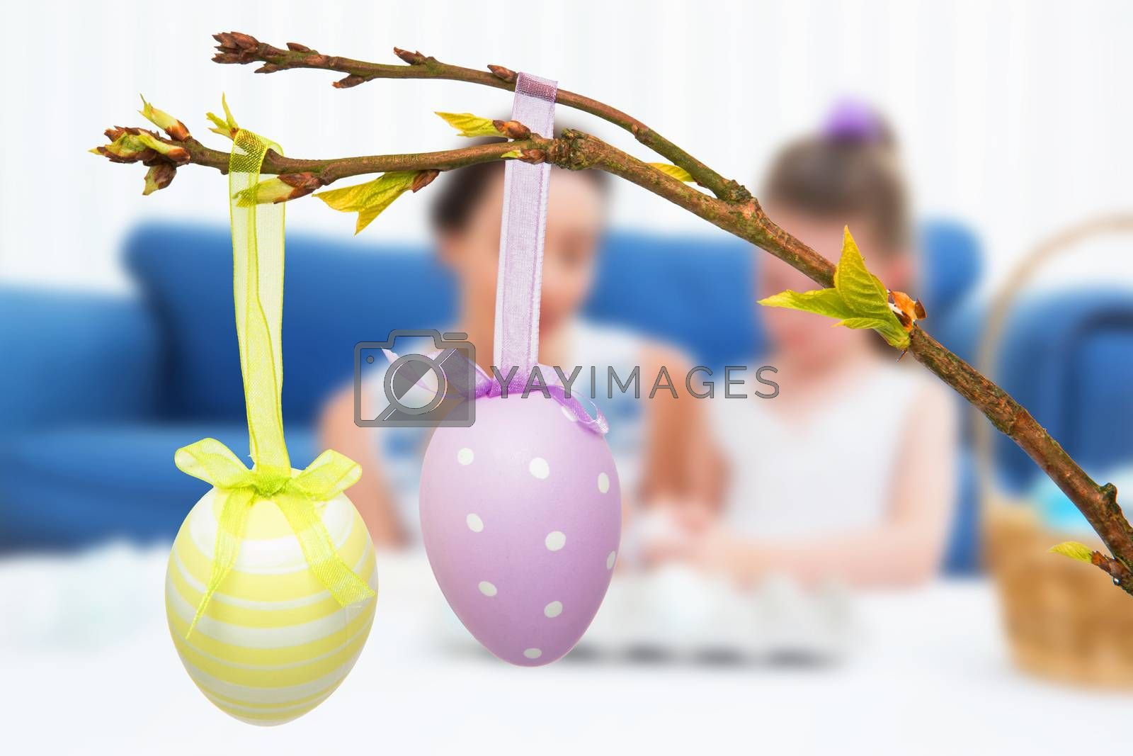 Mother and daughter painting easter eggs against hanging easter eggs