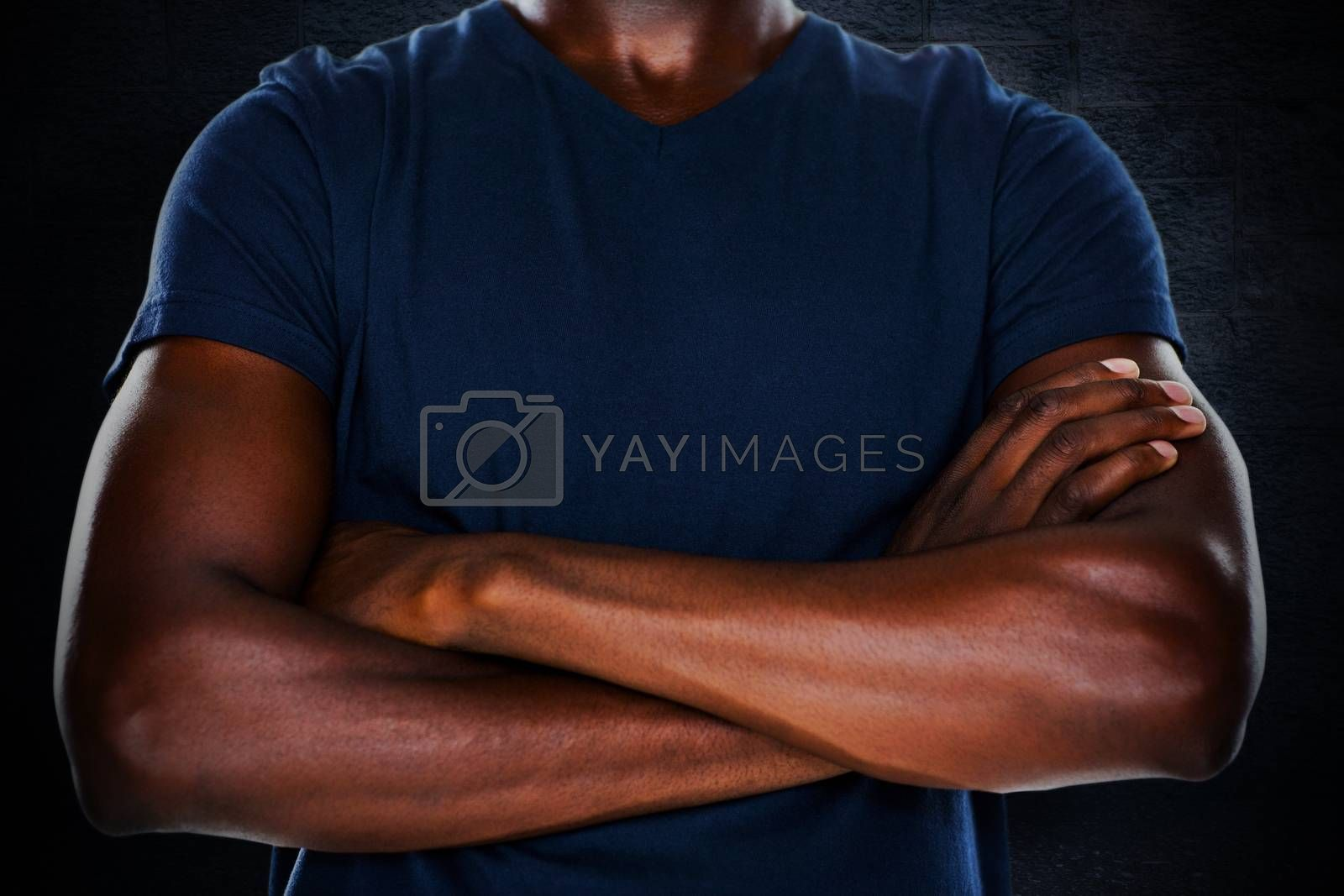 Close up mid section of man with arms crossed against black background