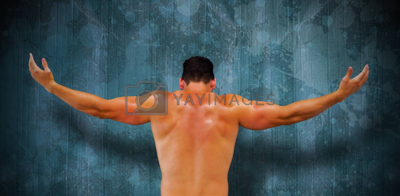 Bodybuilder posing against blue paint splashed surface
