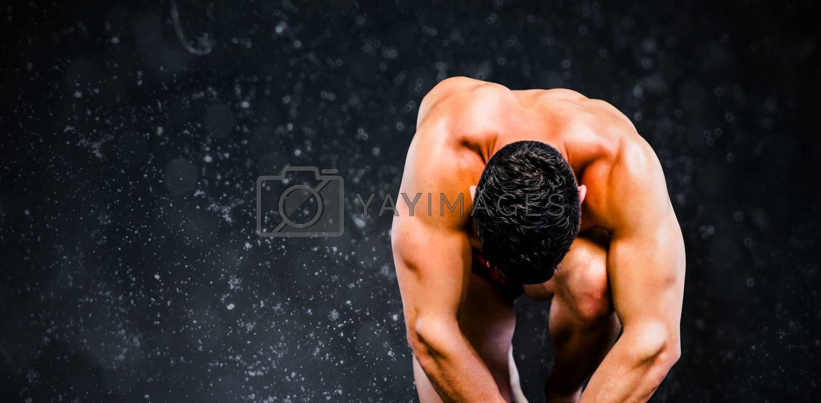 Bodybuilder posing against black background