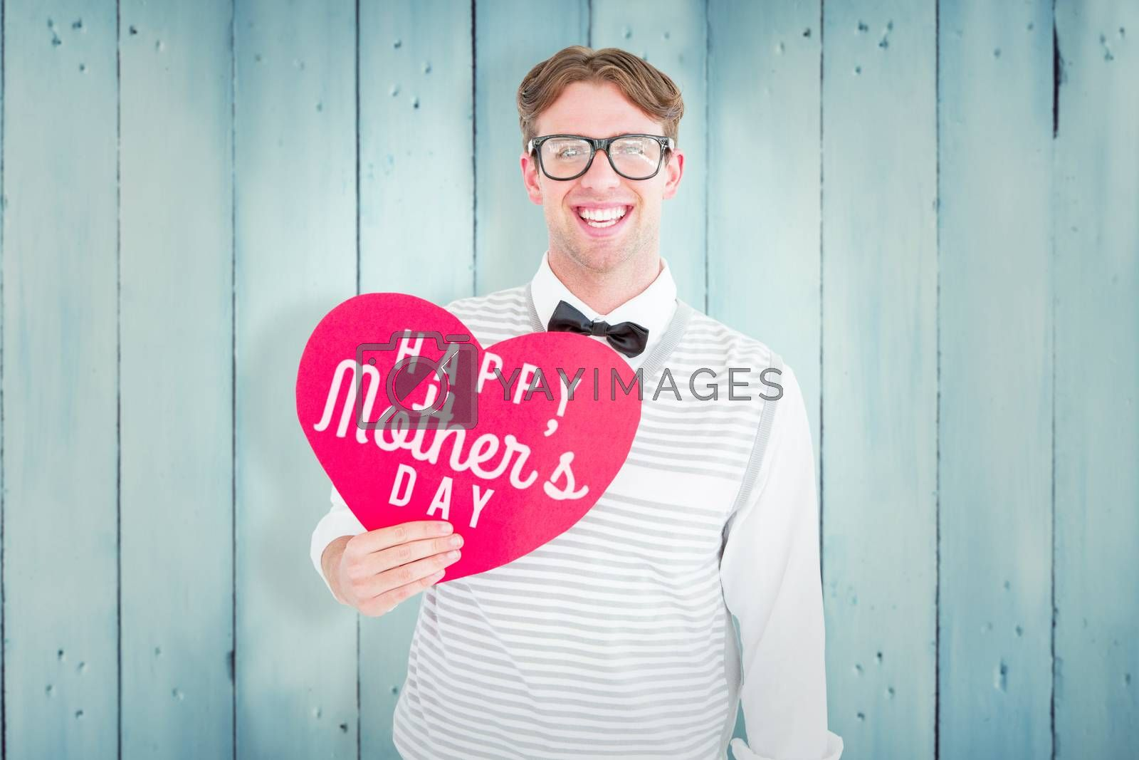 Geeky hipster holding heart card against wooden planks