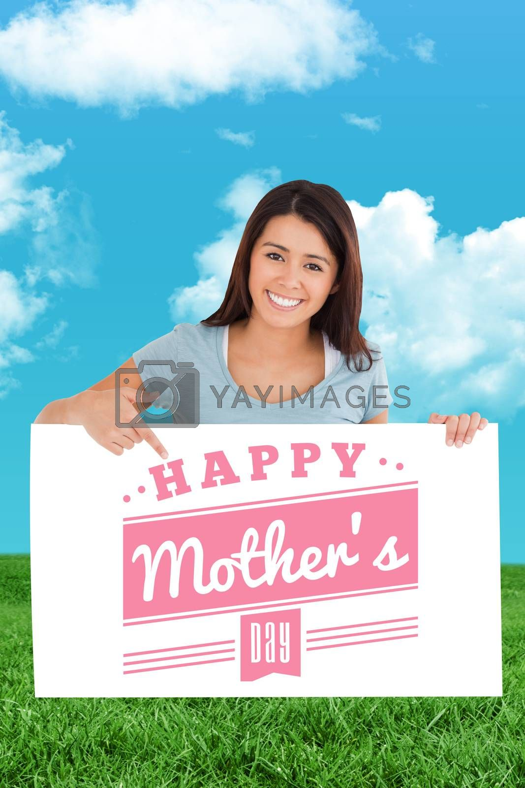 Beautiful woman pointing at a board against field and sky