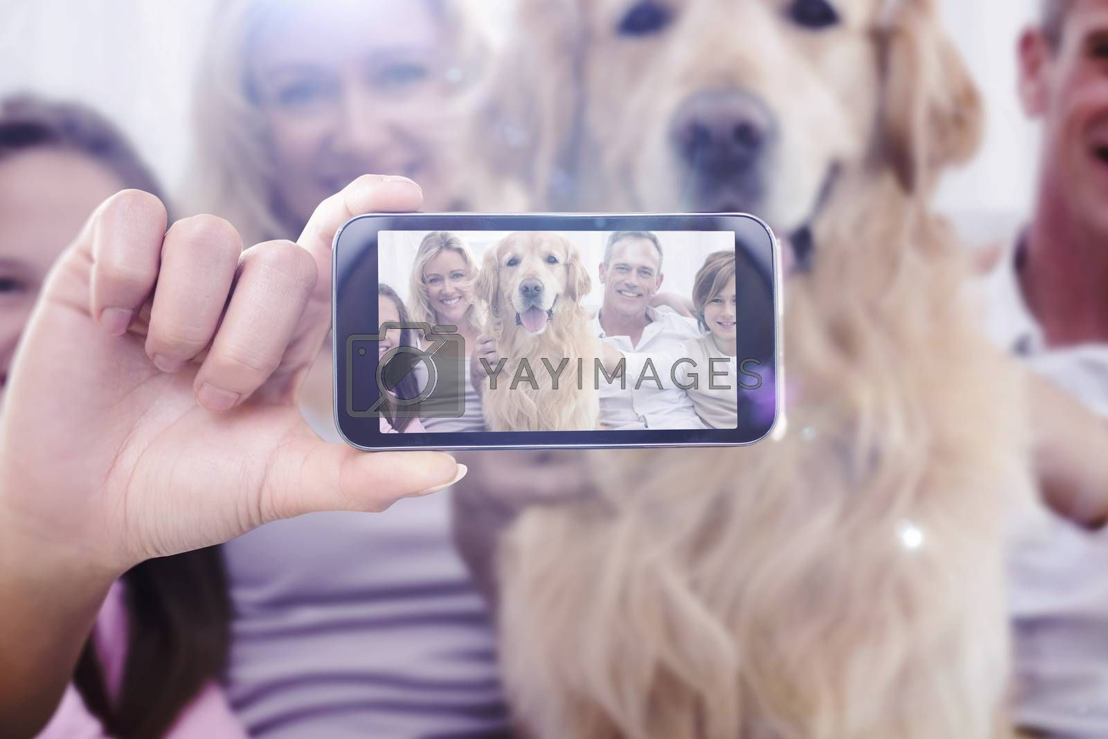 Hand holding smartphone showing against cute family relaxing together on the couch with their dog