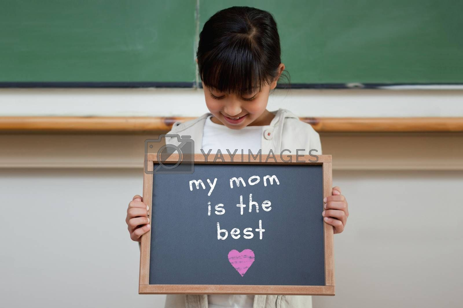 Mothers day greeting against cute pupil showing chalkboard