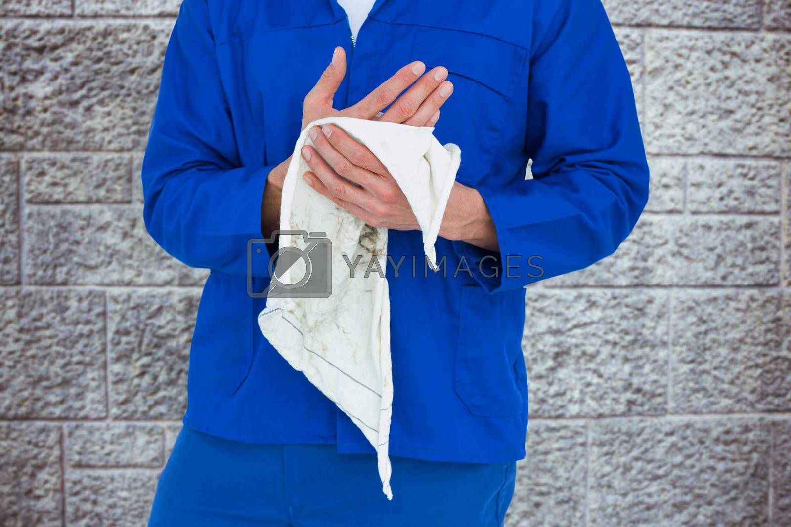 Cropped image of mechanic wiping hand with napkin against grey brick wall