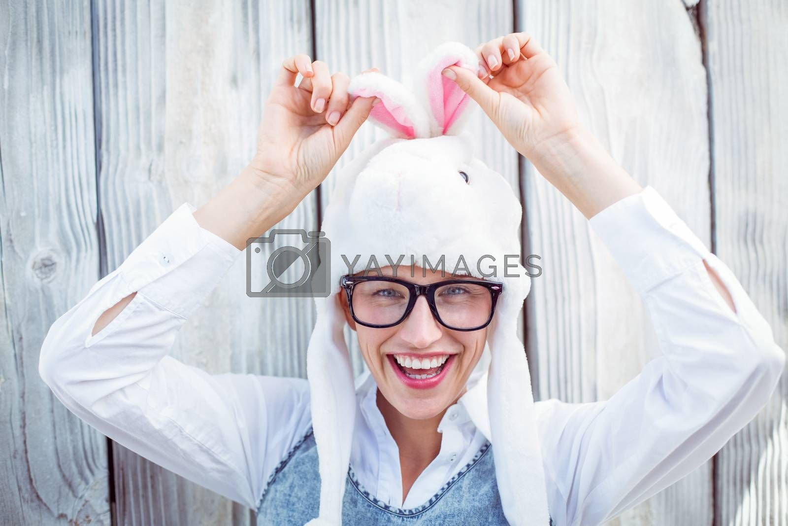 Pretty blonde woman smiling at the camera wearing funny hat on wooden background