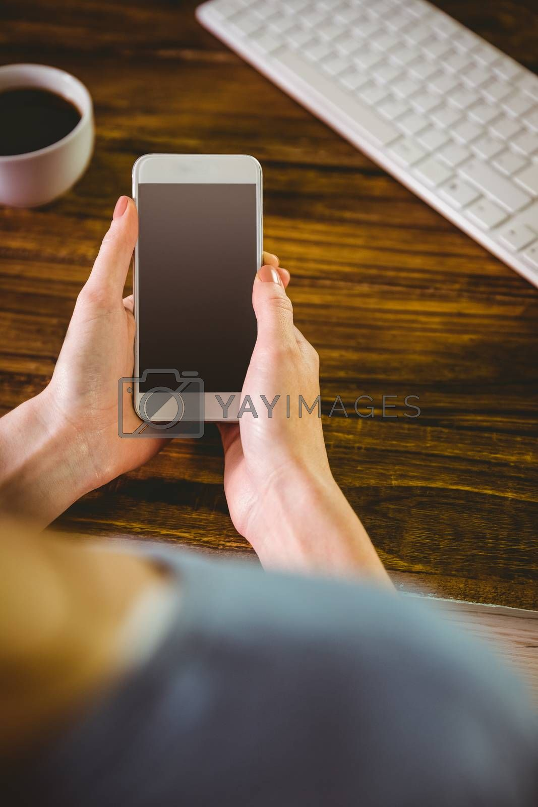 Woman using her smartphone on wooden table