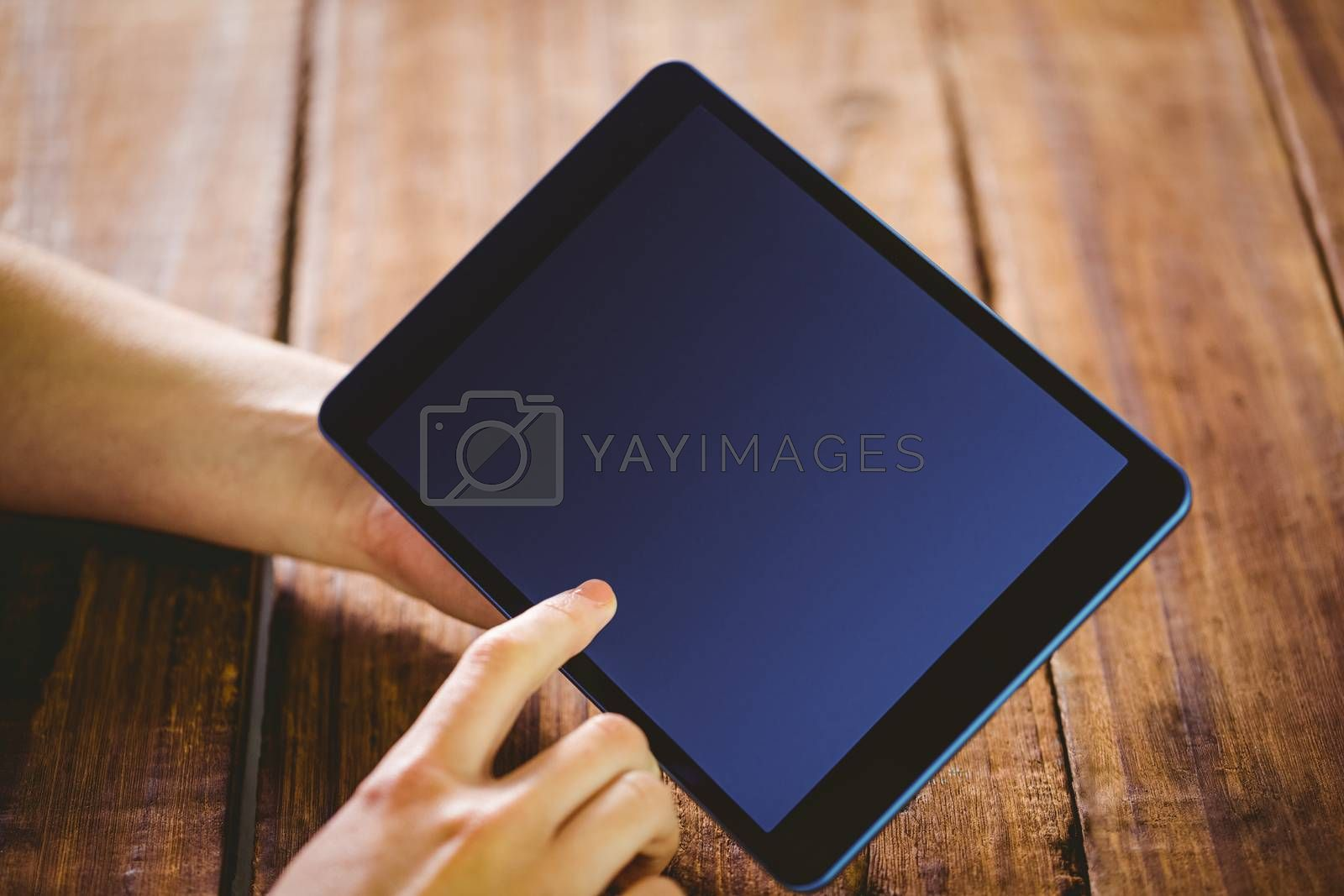 Woman using her tablet pc on wooden table