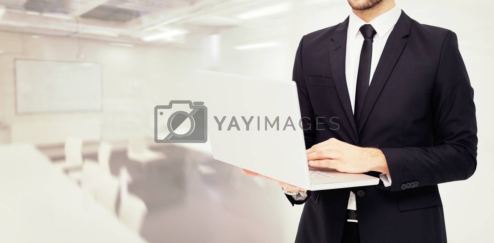 Mid section of a businessman using laptop against classroom