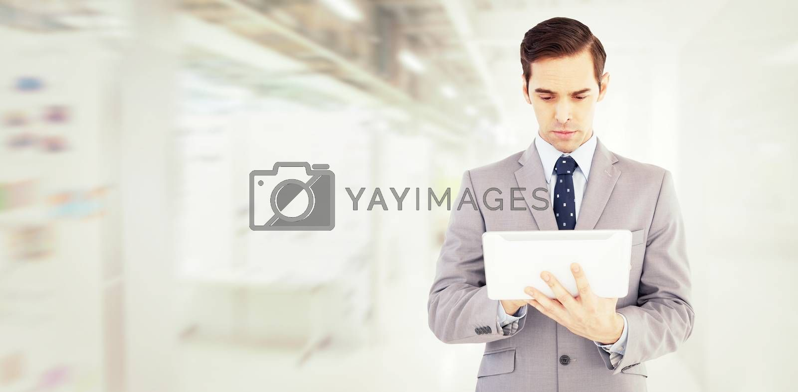 Businessman holding a tablet computer against college hallway