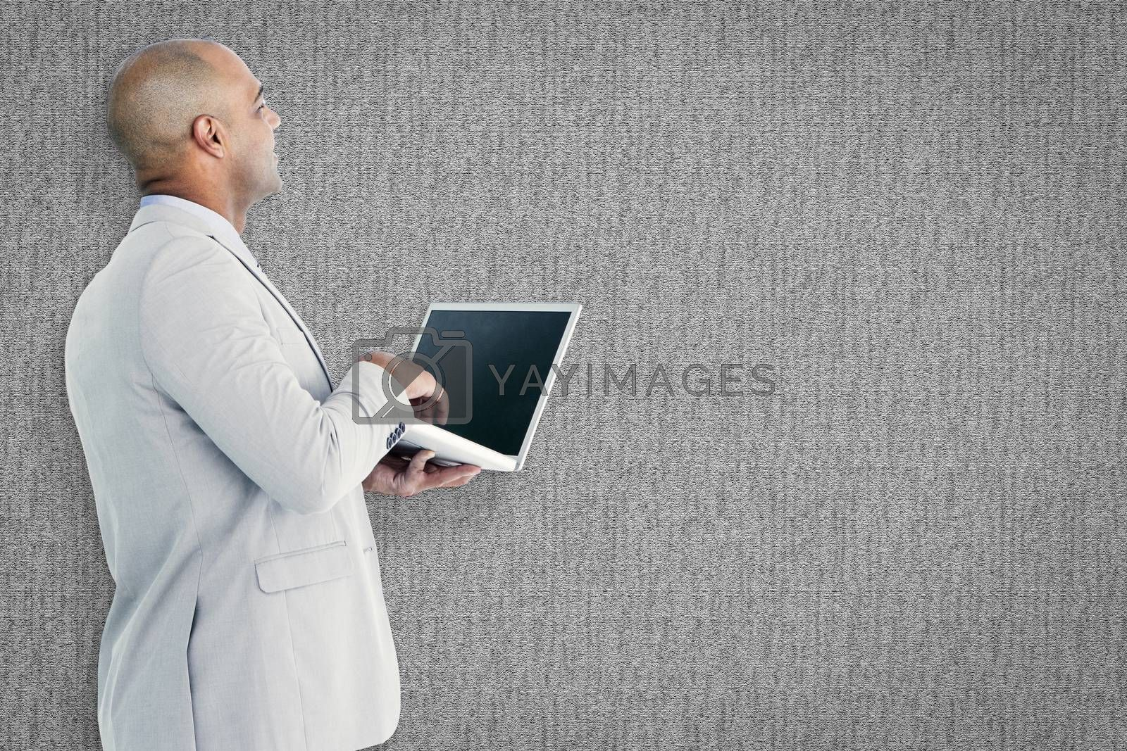 Businessman using laptop against grey background