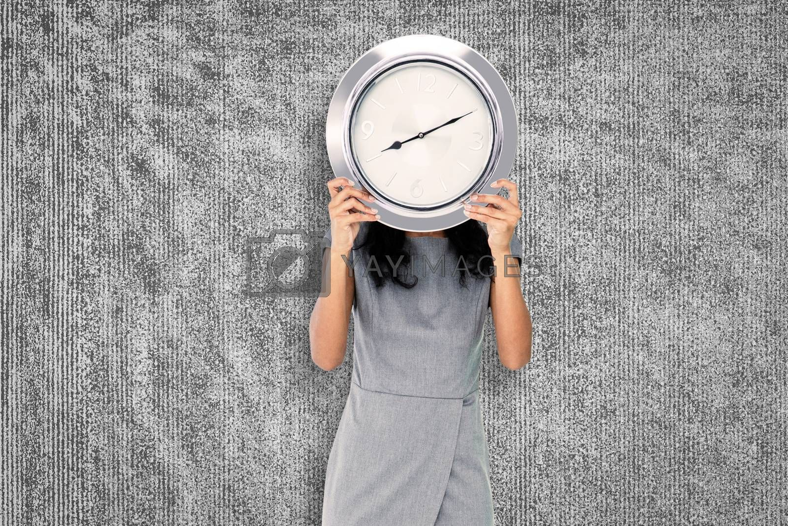Businesswoman holding clock against grey background