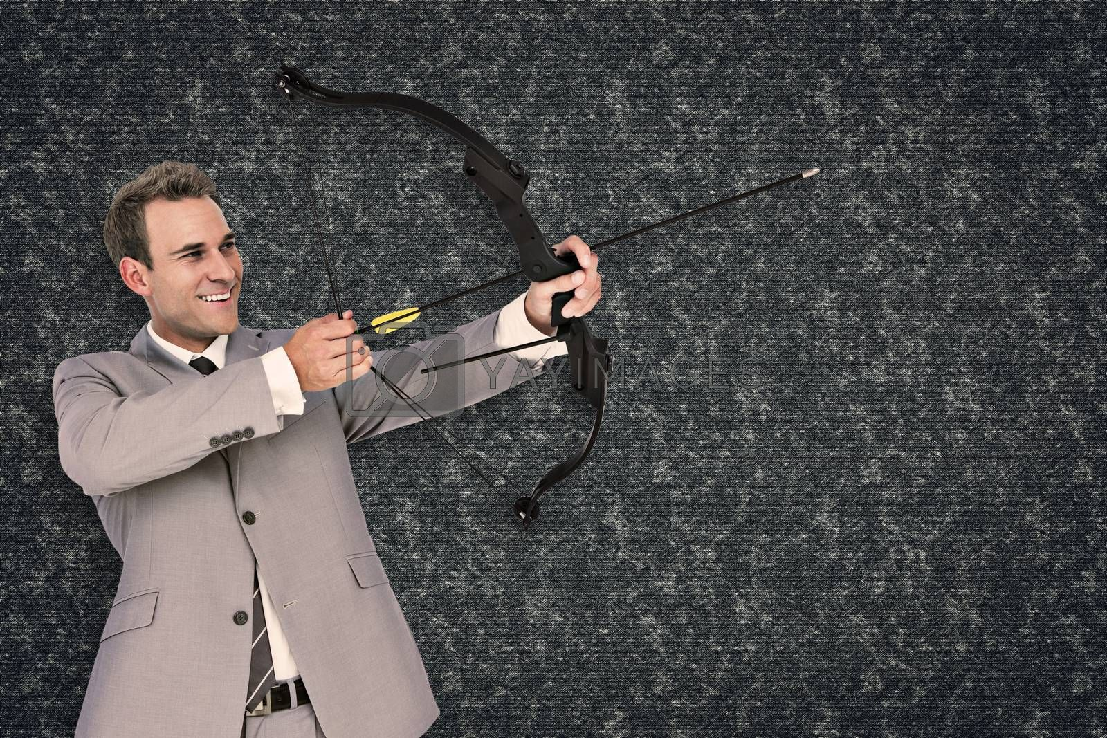 Businessman shooting arrow against black background