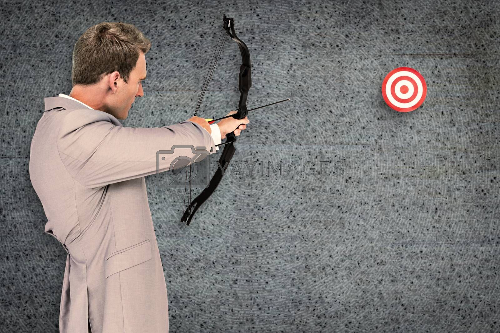 Businessman shooting target against grey background