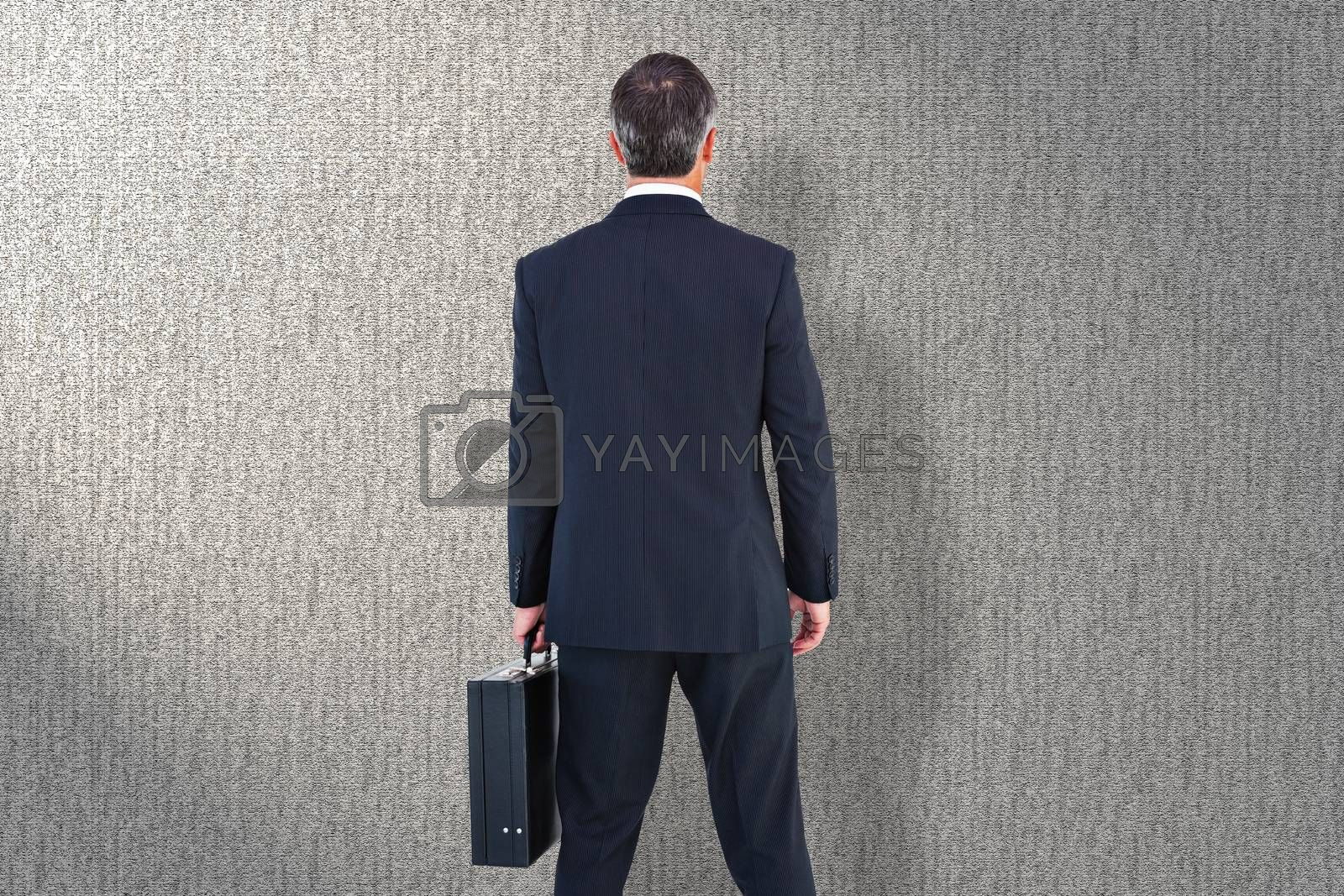 Businessman in suit holding a briefcase against grey background