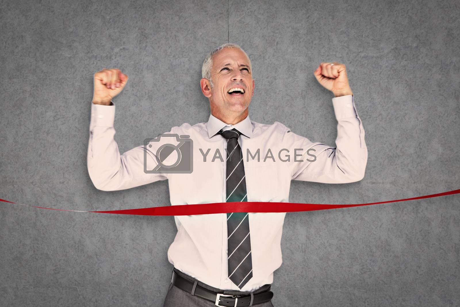 Businessman winning race against grey background