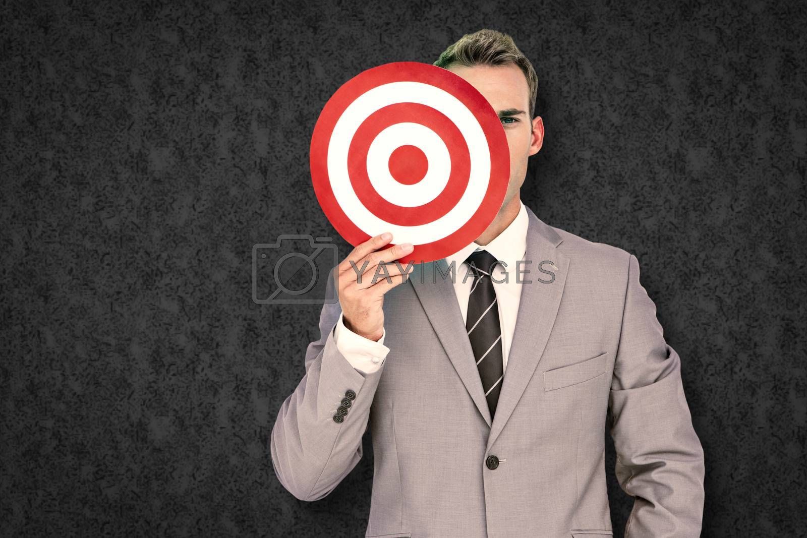 Businessman holding target against grey background
