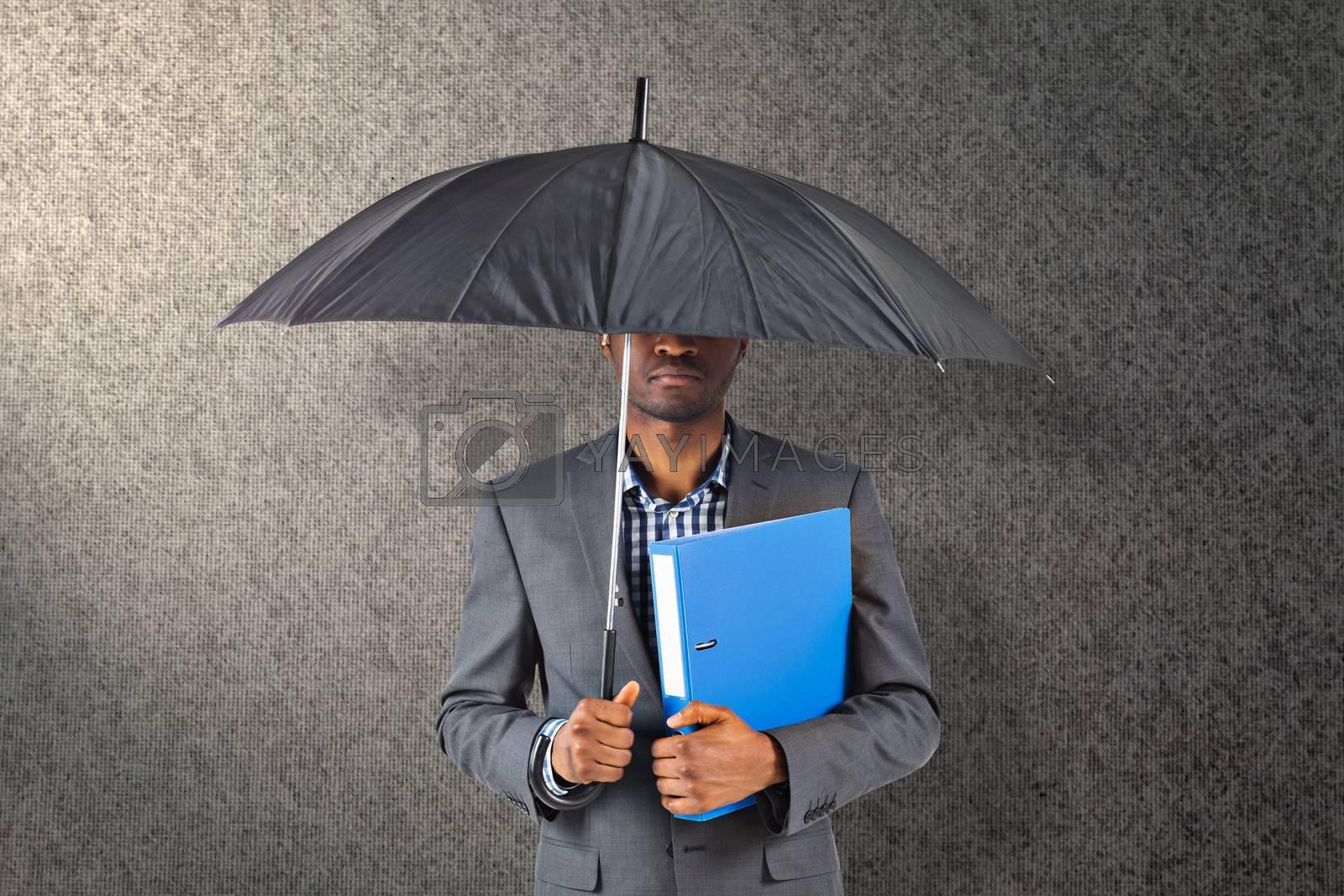 Businessman standing under umbrella against grey background