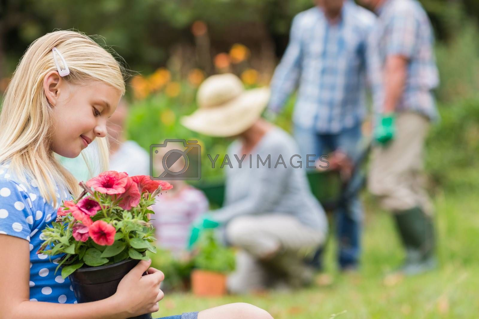 Young girl sitting with flower pot on a sunny day