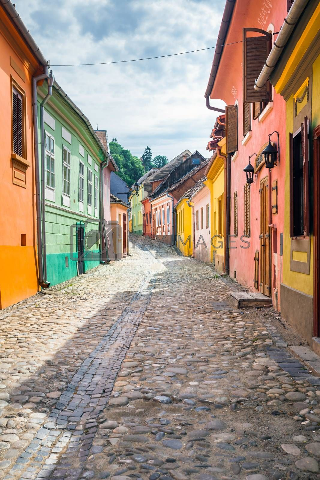Sighisoara, Romania - June 23, 2013: Stone paved old streets with colored houses from Sighisoara fortresss, Transylvania, Romania